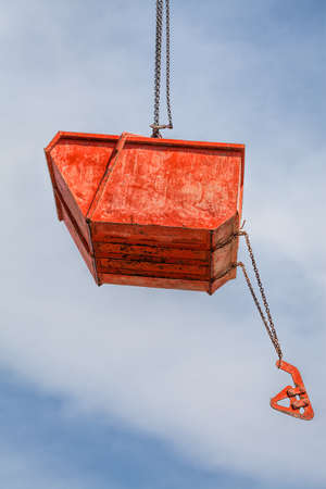 shards: Hanging orange rubble container on build site