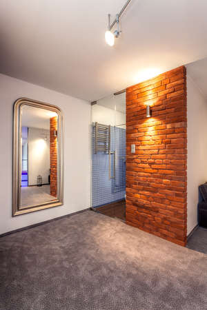 lighted: Brick wall and huge mirror in the modern apartment Stock Photo