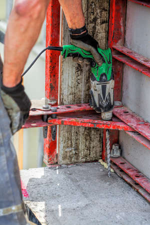 Worker drills holes in building structure photo