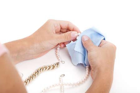 Vrouw schoonmaken van een sieraad met een speciale doek