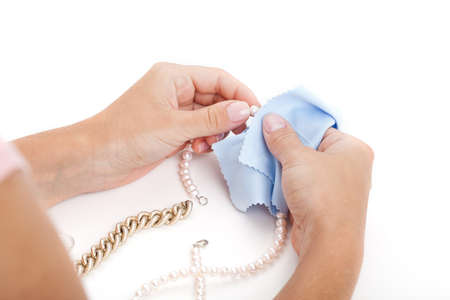 Woman cleaning a jewellery with a special cloth photo