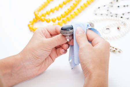 silver jewelry: Polishing silver old-fashioned jewellery with a cloth