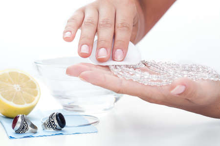 Womans hands cleaning jewellery with a lemon juice