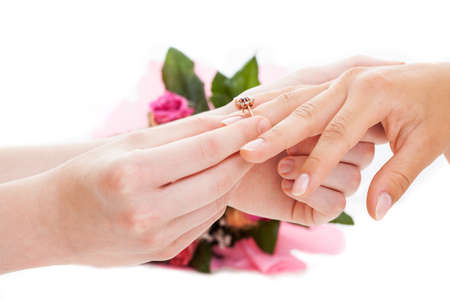 Man putting a golden ring on womans hand, isolated background photo