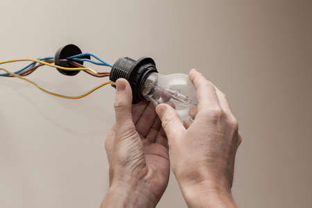 enchufe de luz: Detalle de las manos mans atornillar bombilla nueva