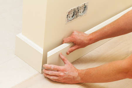 Putting skirting board to a fresh paint wall Stock Photo