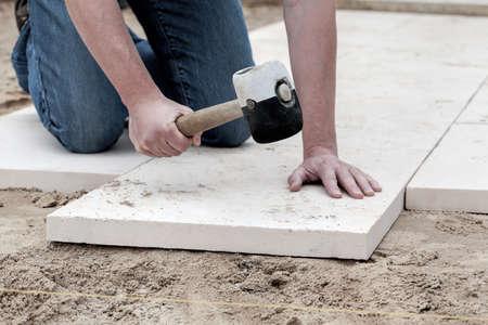 Installatie van tegels met een enorme hamer