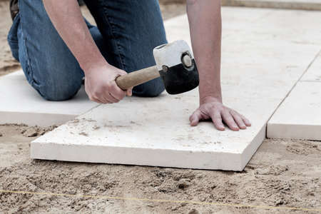 stone work: Installation of paving slabs with a huge hammer