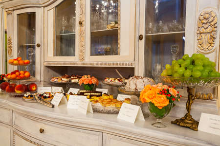 sweet table: Buffet: Cakes on a commode in luxury restaurant