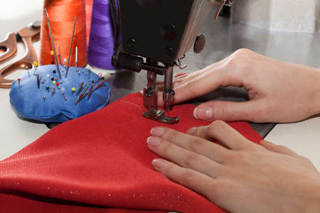 Dressmaker sewing a dress with red material photo