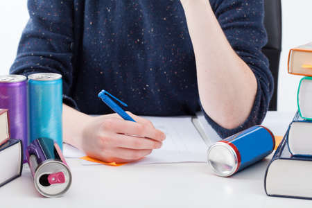energy work: Overworked student with empty cans writing the notes