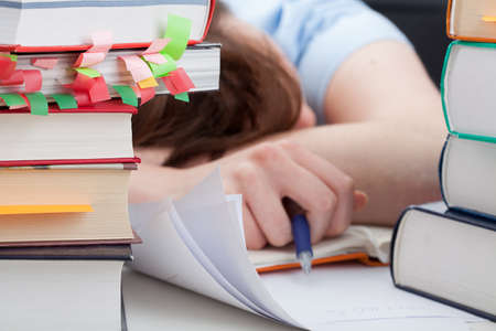Overworked student sleeping on desk around the piles of books photo