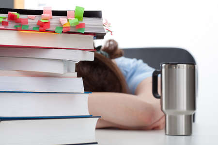 test deadline: Overworked student with coffee and heaps of books on the desk