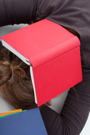 Overworked student sleeping on the desk with a book on her head photo