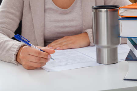 article writing: Academic teacher during writing an article with a coffee and books