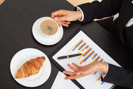 Businessman wtih coffee, croissant and bar chart during explanation photo