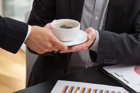 Woman giving a cup of coffee to businessman at the business meeting photo