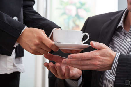 Woman hands giving a cup of coffee to a businessman photo