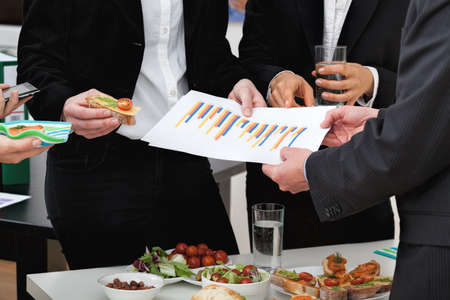 analyze: Managers analyzing chart at a business lunch