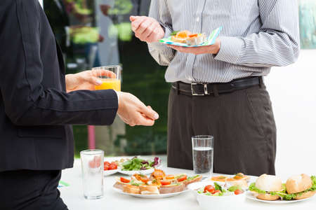 Business colleagues talks during lunch, outdoor photo
