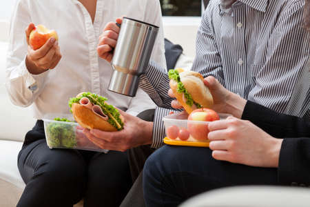 FOOD BOX: Managers eating together homemade meal at work Stock Photo