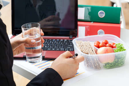 lunch break: Busy manager with glass of water and lunch