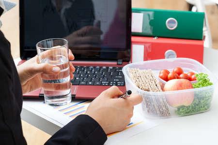 merienda: Encargado ocupado con un vaso de agua y comida