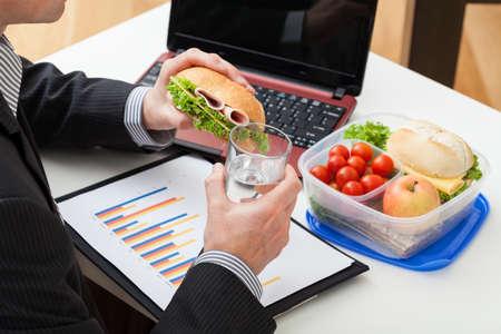 negocios comida: Gerente Trabajador comer un bocadillo durante el trabajo