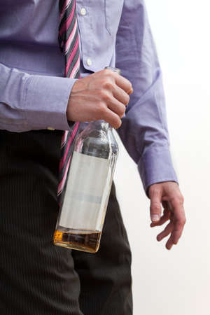 Drunk alone man in suit holding a bottle with alcohol Stock Photo - 22795080