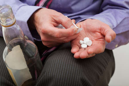 painkillers: Man taking painkillers and drinking alcohol