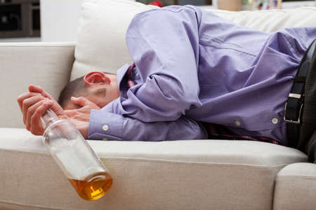 Drunk businessman sleeping with bottle of vodka on a sofa