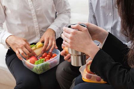 Werknemers met lekkere en gezonde lunch in het kantoor Stockfoto