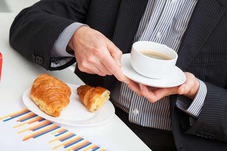 Business break mit Tasse Kaffee und Croissant