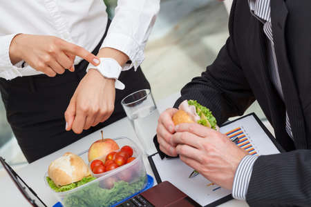 stres: Unhappy manager rushing worker who is having his lunch Stock Photo