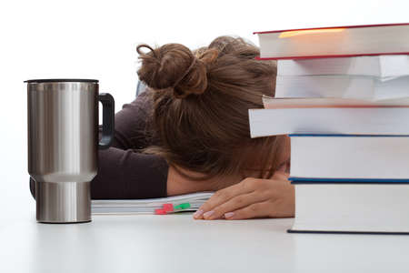 Frustrated student sleeping with a coffee around the books photo