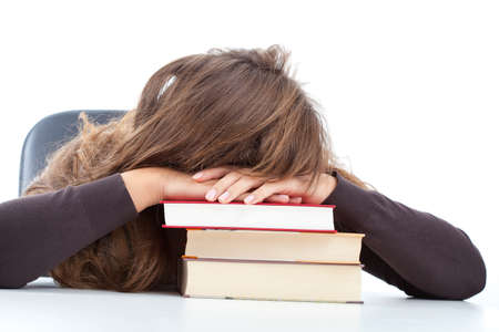 test deadline: Fatigued pupil sleeping on the stack of books