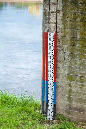 depth measurement: A water level measure on a brick wall by a river