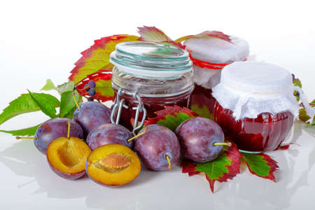 Homemade plum jams in jars with fresh plums and autumn leafs on background Stock Photo - 23007197