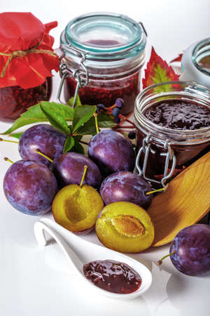 Juicy plums and opened jars with jams Stock Photo - 23007198