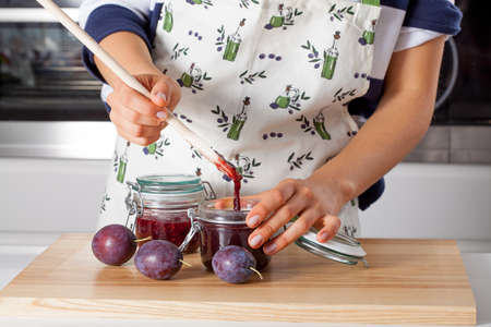 Housewife filling the jar with homemade jam Stock Photo - 23049375