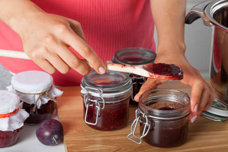 Housewife preparing fresh homemade plum jam photo
