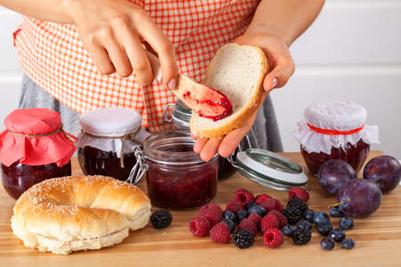 Woman spreading the bread with jam for breakfast Stock Photo - 23049381