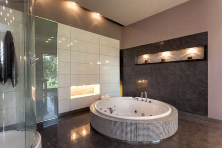 modern interior architecture: Round bath in a luxury tiled bathroom interior