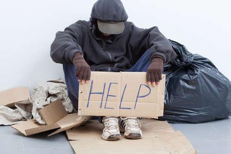 persona: El hombre sin hogar que se sienta en una calle con señal Foto de archivo