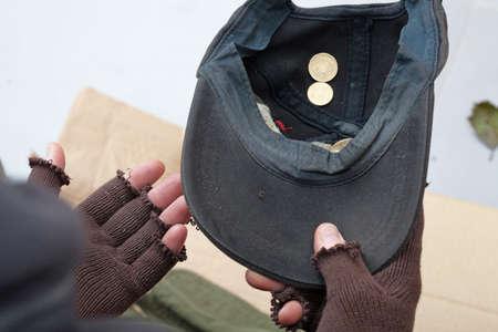 limosna: Pobre hombre sosteniendo una taza y pidiendo limosna