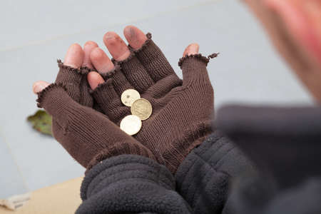 彼の手には、数セントを保持しているホームレスの人