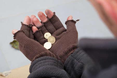 vagabundos: Persona sin hogar que sostiene unos pocos centavos en sus manos