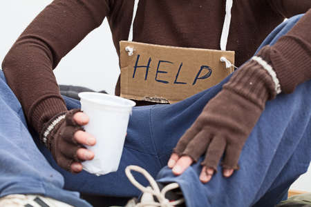 Male homeless sitting on a street with sign asking for help Stock Photo - 23049400
