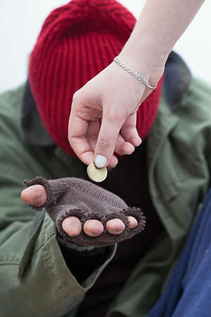 homeless person: Women giving a coin for homeless poor man