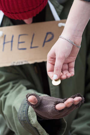 poor man: Rich woman giving a coin to homeless man in need